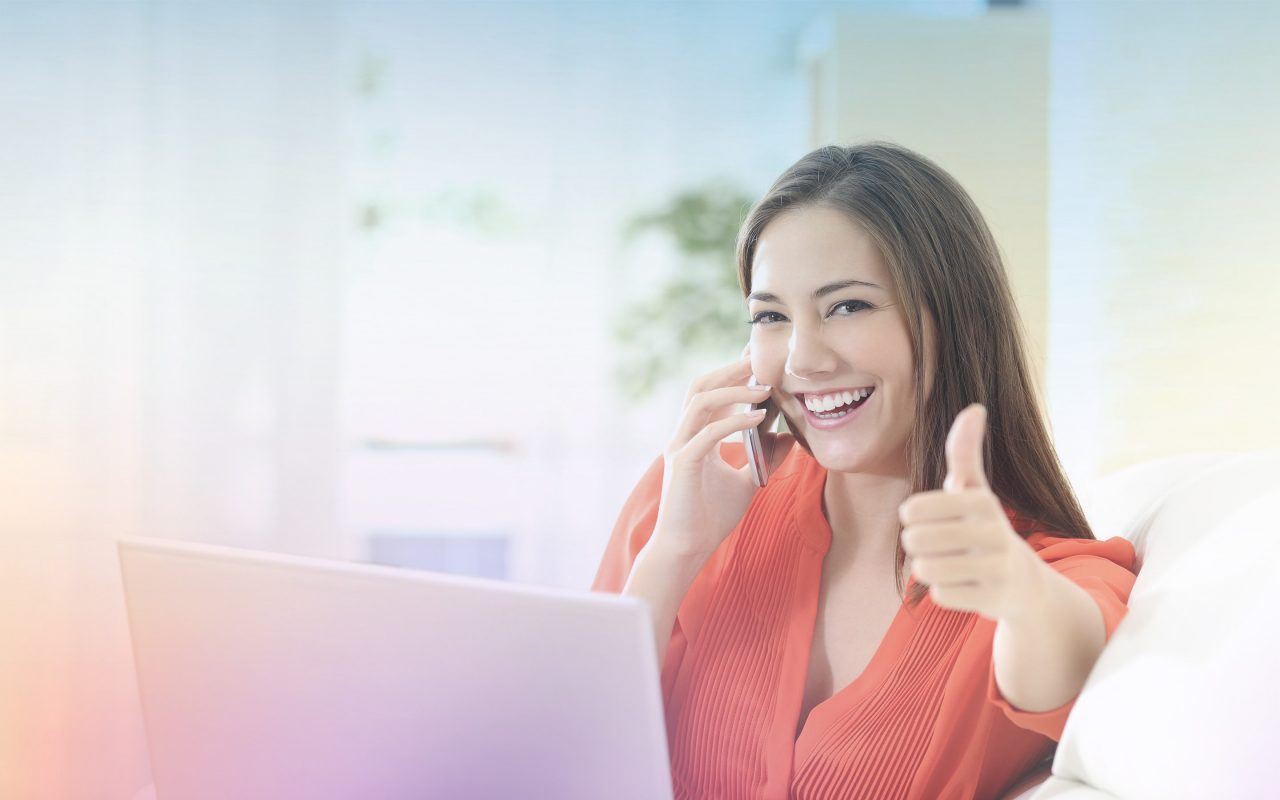 Arvato Systems_Commerce_Thumbs-up-woman with smartphone in front of laptop