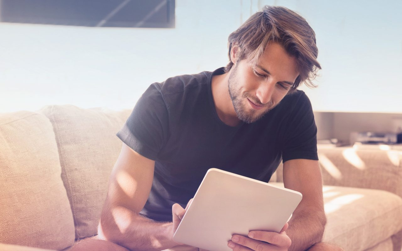 Arvato Systems_Commerce_Man on couch looking on tablet smiling